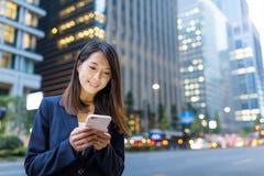 Польза коммерсантки мобильного телефона на городе токио Стоковая Фотография RF