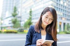 Польза коммерсантки мобильного телефона на улице токио Стоковые Фотографии RF