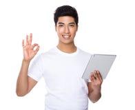 Польза молодого человека таблетки и одобренного знака Стоковое фото RF