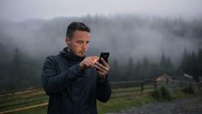 Польза молодого человека телефон в вечере в горах Вокруг леса в тумане видеоматериал