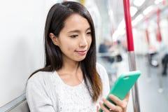Польза молодой женщины умного телефона внутри метро Стоковые Изображения