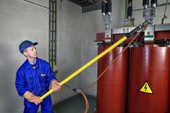 Пользы работника изолируя штангу к заземлительному трансформатору земли Стоковые Фото