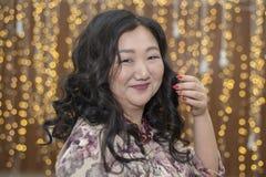 Польностью азиатская женщина на предпосылке накалять освещает стоковое фото