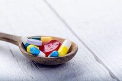 Польностью деревянная ложка таблеток Предпосылка фармации на белой таблице Таблетки на белой предпосылке Пилюльки Медицина и здор Стоковые Фото