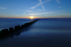 Польша, прибалтийская над заходом солнца моря Волнорез на ровной поверхности моря Стоковые Фото