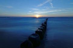 Польша, прибалтийская над заходом солнца моря Волнорез на ровной поверхности моря Стоковое Фото