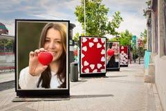 Полюбите афиши, фотоснимки женщины с красным сердцем, на городе Стоковое фото RF