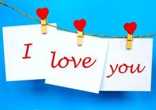 Полюбите вас текст на стикерах вися на штырях формы сердца Стоковые Изображения