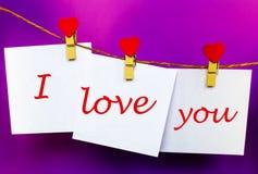 Полюбите вас текст на стикерах вися на штырях формы сердца Стоковые Фотографии RF