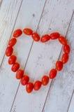 полюбите знак Сердце сделанное от малых томатов Стоковые Фото