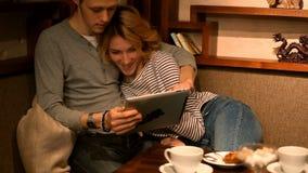 Полюбите парня и девушка сидя на таблице, использует таблетки видеоматериал
