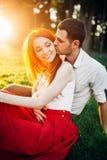Полюбите пар целуя в парке лета на заходе солнца Стоковое Фото