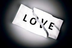 Полюбите слово написанное на сорванной бумаге на белизне Стоковое Фото