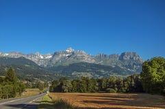 Поля, дорога, лес, высокогорный ландшафт и голубое небо в Свят-Gervais-Les-Bains стоковая фотография rf