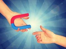 Правая рука принимая голубой и красный магнит стоковая фотография rf