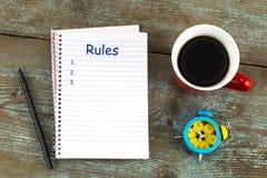 Правила перечисляют с тетрадью, чашкой кофе на деревянном столе верхняя часть соперничает Стоковое фото RF