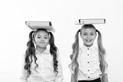 Правильная позиция Школьницы с милым стилем причёсок хвостов носят папки на головах Совершенные школьницы с аккуратной вычурой стоковое изображение rf