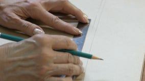 Правитель и карандаш белошвейки в руке делают чертежи для одежд Стиль и проектная модификация и одежда создания акции видеоматериалы