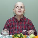 Правильное питание после химиотерапии Облыселая женщина на таблице есть брокколи, плодоовощ Стоковое Изображение