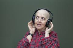 Правильное питание после химиотерапии Облыселая женщина на таблице есть брокколи, плодоовощ Стоковая Фотография