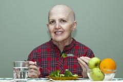 Правильное питание после химиотерапии Облыселая женщина на таблице есть брокколи, плодоовощ Стоковые Фото
