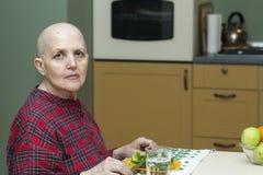 Правильное питание после химиотерапии Облыселая женщина на таблице есть брокколи, плодоовощ Стоковое Изображение RF