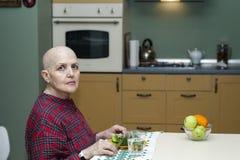 Правильное питание после химиотерапии Облыселая женщина на таблице есть брокколи, плодоовощ Стоковые Изображения