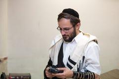 Правоверный еврей очищает место tefillin после молитв Стоковые Фото
