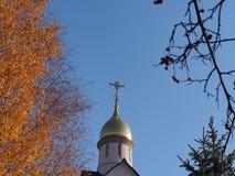 Правоверный крест обрамленный желтыми листьями осени деревьев стоковые изображения rf