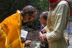 Правоверный священник во время таинства духовного рождения - крещения Стоковое Изображение RF