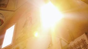 Правоверный, христианство, церковь Солнце светит от вершины окна в старой церков с религиозными искусствами на стене сток-видео