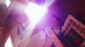Правоверный, христианство, церковь Солнце светит от вершины окна в старой церков с религиозными искусствами на стене видеоматериал
