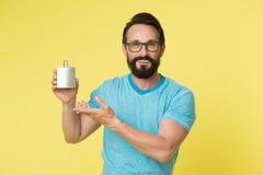 Правое благоухание дух делает вас молодой Дух бутылки владением стороны человека бородатый красивый усмехаясь defocused Как выбра Стоковые Фото