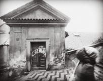 ПРАГА, ЧЕХИЯ: девушка вверх по лестницам, проходя старыми пропускающими влагу низкими домами Стены падают врозь, scribbled дверь Стоковое фото RF