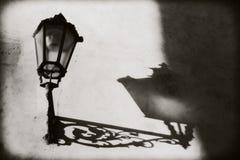 Прага, чехия: Не освещенный фонарик на стене От его на стене произнесл тень и планы Стоковые Изображения RF