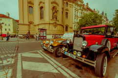 Прага, чехия - 13-ое августа 2015: 2 классических красивых автомобиля припарковали на улице поперек от известной церков Стоковые Фото