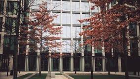 ПРАГА, ЧЕХИЯ - 3-ЬЕ ДЕКАБРЯ 2016 Оранжевые и безлистные деревья осени против современного стеклянного делового центра фасада стоковые изображения rf