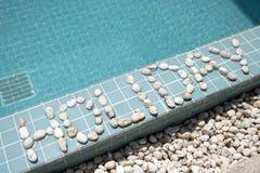 ` Праздника ` надписи положено вне камешком на сторону бассейна стоковые изображения