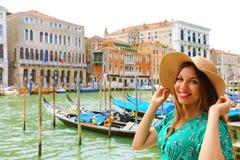 Праздники в Венеции! Красивая женщина с соломенной шляпой усмехаясь на камере с каналом, гондолами и дворцами Венеции грандиозным стоковое изображение rf