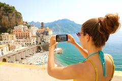 Праздники в Италии! Красивая молодая женщина фотографирует с умным телефоном деревни Atrani на побережье Амальфи, Италии стоковое изображение