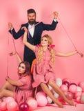 праздники и куклы засилье и зависимость творческая идея Любовный треугольник ретро девушки и мастер в воздушных шарах партии стоковая фотография rf