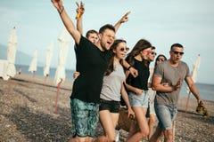 праздники, каникулы группа в составе друзья имея потеху на пляже, идти, пиве питья, усмехаться и обнимать стоковые фотографии rf
