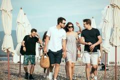 праздники, каникулы группа в составе друзья имея потеху на пляже, идти, пиве питья, усмехаться и обнимать стоковое изображение rf