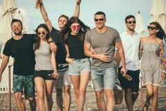 праздники, каникулы группа в составе друзья имея потеху на пляже, идти, пиве питья, усмехаться и обнимать стоковое фото rf