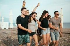праздники, каникулы группа в составе друзья имея потеху на пляже, идти, пиве питья, усмехаться и обнимать стоковые фото