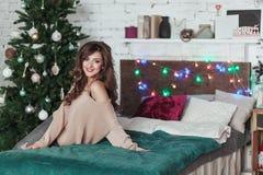 Праздники рождества Милая девушка брюнет сидит на кровати Спальня просторной квартиры украшенная с гирляндами и елью рождества Стоковое фото RF