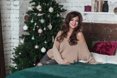 Праздники рождества Милая девушка брюнет сидит на кровати Спальня просторной квартиры украшенная с гирляндами и елью рождества Стоковые Изображения RF