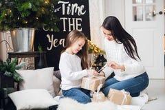 праздники рождества счастливые веселые Жизнерадостная мама и ее милая девушка дочери обменивая подарки Родительский и маленький р стоковая фотография