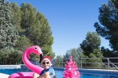 Праздники счастливого рождеств в теплых странах Милый ребенок нося шляпу Санта бассейном с розовым деревом xmas стоковое изображение