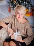 Праздники ` s Нового Года, девушка сидит на кресле смотря вверх с подарком в руках Стоковое Фото